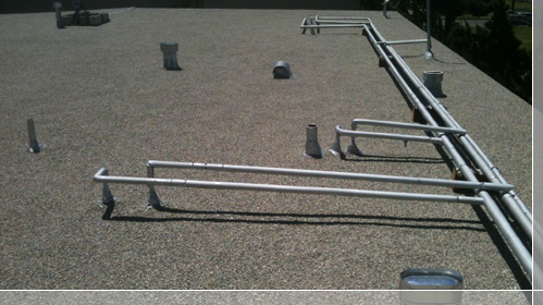 Plumbing pipes running the roof with insulation and coating applied - El Segundo